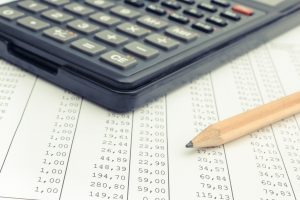 Calculator and pencil on spreadsheet. Business concept